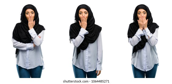 Arab woman wearing hijab covers mouth in shock, looks shy, expressing silence and mistake concepts, scared isolated over white background