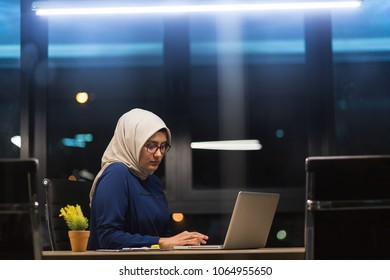Arab Woman wearing hijab working overtime in modern designed office.