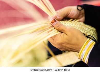 An Arab woman is weaving palm leaves to make traditional arts and crafts. hand made crafts.Close up of old woman's hand at work.