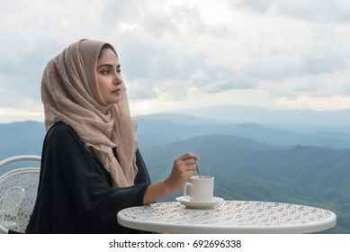 Arab women in hijab holding coffee sitting on the background of mountain and looking at camera. woman is dressed in a black and  scarf brown.