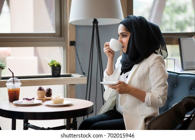 Arab women in hijab holding and drinking coffee cup sitting in the coffee shop.