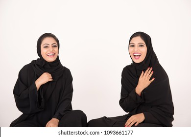 Arab women sitting on the floor talking with white background