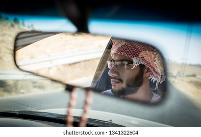 Arab young man driving car on road