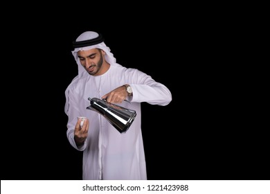 Arab young man serving Arabic coffee for his guests
