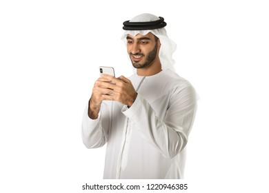 Arab young man using mobile standing on white background. Technology concept smartphone.