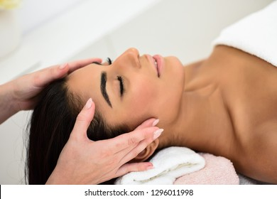 Arab young woman receiving head massage in spa wellness center. Beauty and Aesthetic concepts.