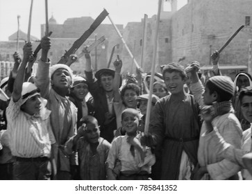 Arab youths with sticks and clubs cheering the burning of the police barracks and post office. Bethlehem, Palestine, Oct. 8, 1938