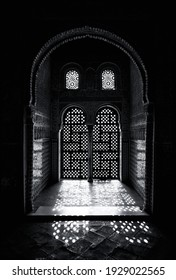 Arabesque style ornate window detail, with sunlight shining through. Black and white.