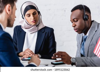 arabian and african american business people in headsets near digital translators and interpreter on blurred foreground