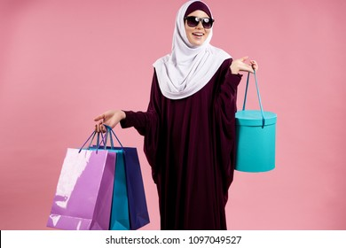 Arabian attractive woman in sunglasses holds paper colored bags. Shopping and consumerism concept. Isolated on pink background.