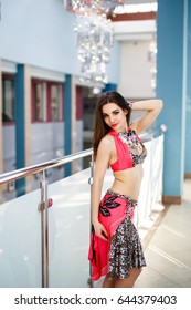 Arabian belly dancer woman in colorful costume indoor portrait. The girl turned to the camera. Pink costume with jewels.