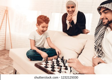 Arabian Boy Playing Chess with Father at Home. Healthy Lifestyle Concept. Smiling Mother. Muslim Family. Smiling Boy at Home. Young Arabian Man. Board Game. Father and Son. Indoor Fun.