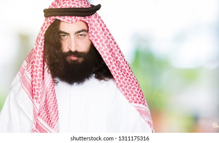 Arabian business man with long hair wearing traditional keffiyeh scarf skeptic and nervous, frowning upset because of problem. Negative person.