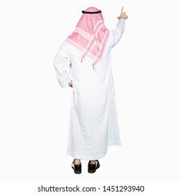 Arabian business man with long hair wearing traditional keffiyeh scarf Posing backwards pointing behind with finger hand