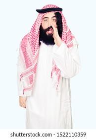 Arabian business man with long hair wearing traditional keffiyeh scarf hand on mouth telling secret rumor, whispering malicious talk conversation