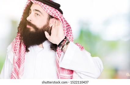 Arabian business man with long hair wearing traditional keffiyeh scarf smiling with hand over ear listening an hearing to rumor or gossip. Deafness concept.
