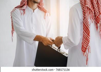 Arabian business man transfer deal after finishing up a business meeting in office, handover of a briefcase in hand of partner, successful, meeting, partner, teamwork, community, connection concept