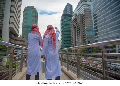 Arabian business people with briefcase walking together in teamwork, Saudi Arabian business concept.