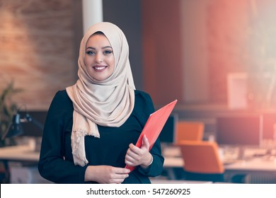 Arabian business woman holding a folder in modern startup office