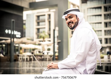 Arabian businessman with laptop working outdoor