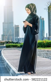 Arabian businessman reading a message. Arab businesswoman hijab holding cell phone on the street on a background of skyscrapers of Dubai. The woman is dressed in a black abaya