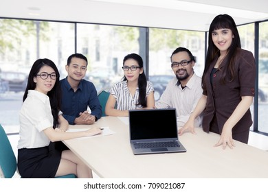Arabian businesswoman showing a blank laptop while standing in the conference room with her friends