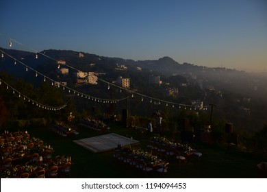 Arabian Celebration Preparation in the top of mountain in Jounieh / Lebanon - tablets and chairs and light on the grass and Mountain clouds in background