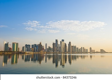 Arabian city of Doha Qatar, where the skyline changed drastically over the past 5 years. Image captured early in the morning with the sun rising from the right and some rare fluffy clouds in the sky..