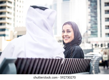 Arabian couple portrait. Man and woman with arabic traditional clothes speaking on a bench
