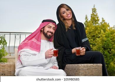 arabian couple relaxing in the garden drinking tea