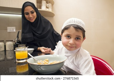 Arabian family of mom and son having breakfast in the kitchen