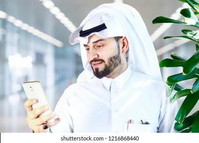 Arabian (Gulf area) smiling man with traditional wear and using a mobile phone.