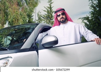 arabian guy posing against his car at home