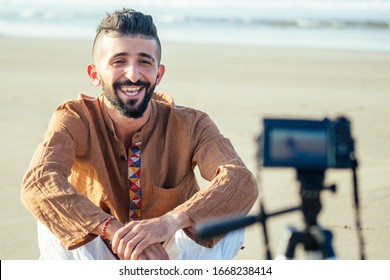 arabian man sitting on sand and talking tripod video making in beach. Travel videographer lifestyle content maker concept