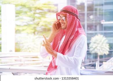 Arabian man is talking on the phone happily.