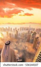 Arabian man watching Dubai Marina covered by early morning fog in Dubai, United Arab Emirates