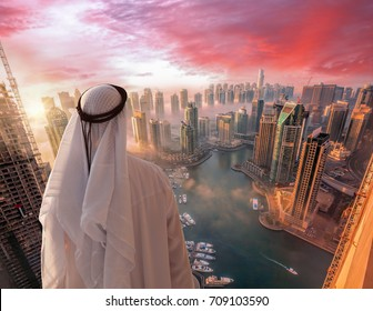 Arabian man watching  Dubai marina  in Dubai, United Arab Emirates.