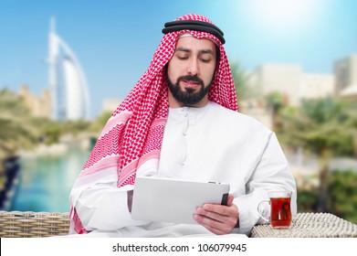 arabian man working on a mobile tablet & drinking tea