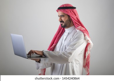 Arabian man working on a notebook, Arabian businessman with laptop against white background