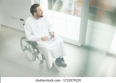 Arabian middle aged man in wheelchair at home