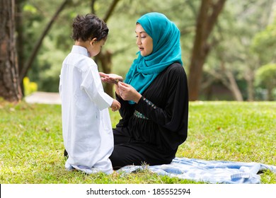 Arabian mother playing with little boy outdoors