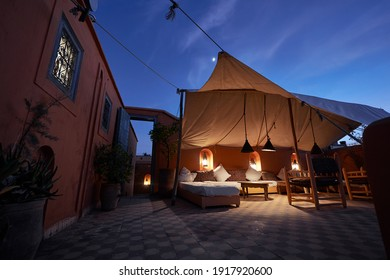 Arabian night. Traveling by Morocco. Relaxing in festive moroccan traditional riad interior in medina. Comfortable terrace filled with soft, cozy furniture.