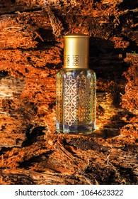 Arabian perfumes on the background of bark. Arabian oud attar perfume or agarwood oil fragrances in mini bottle.