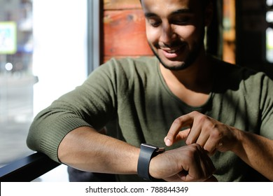 Arabian sits near window and uses smart watch in caf . Person dressed in khaki pullover and white jeans. Boy has dimples, beard, full lips and black hair. Concept of modern technologies and good