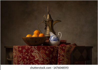 Arabian themed still life of a middle eastern  coffee pot, pitcher and oranges created like an old master painting.