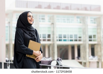 Arabian woman holding a book and smiling, looking aside.