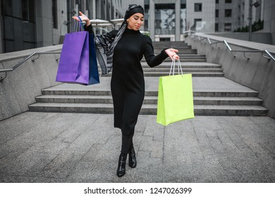 Arabian woman poses. She stands and hold colorful shopping bags in hands. She wears black dress and hijab.