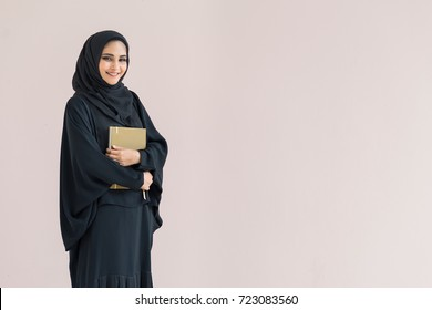 Arabian woman standing and holding a book.