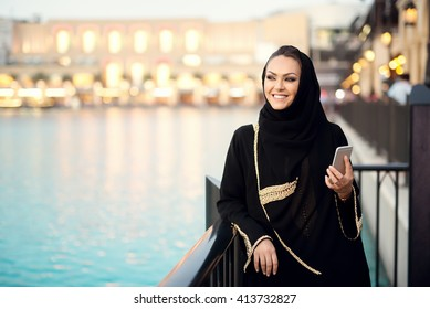 Arabian woman typing on smart phone and smiling, looking aside.