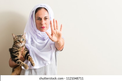 Arabian woman wearing white hijab holding a cat with open hand doing stop sign with serious and confident expression, defense gesture